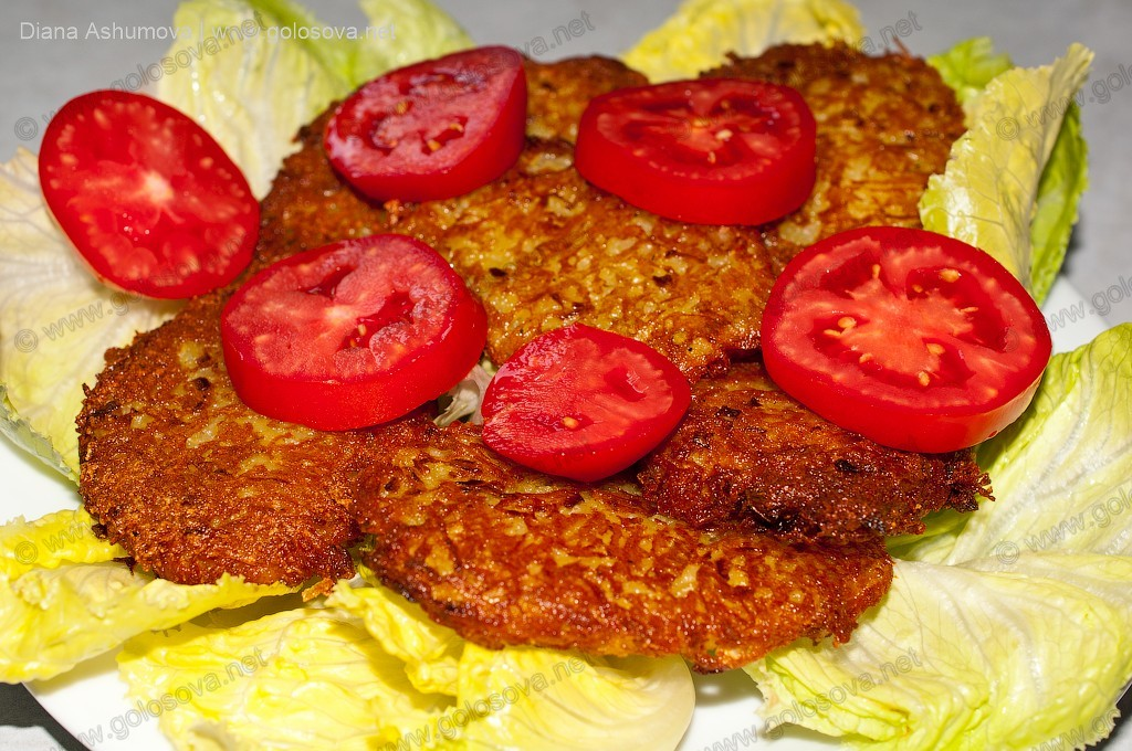 картофельный котлеты с помидорами черри на листьях салата