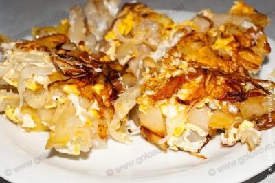 жареный картофель с яйцами и луком на тарелке