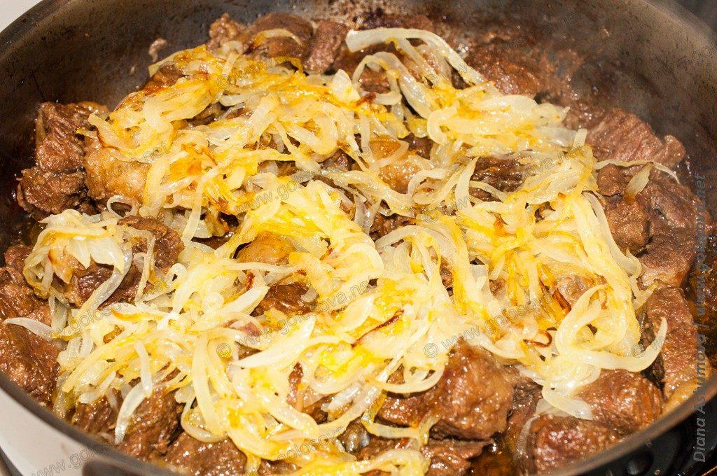 тушеная говядина с обжаренным луком в сковороде