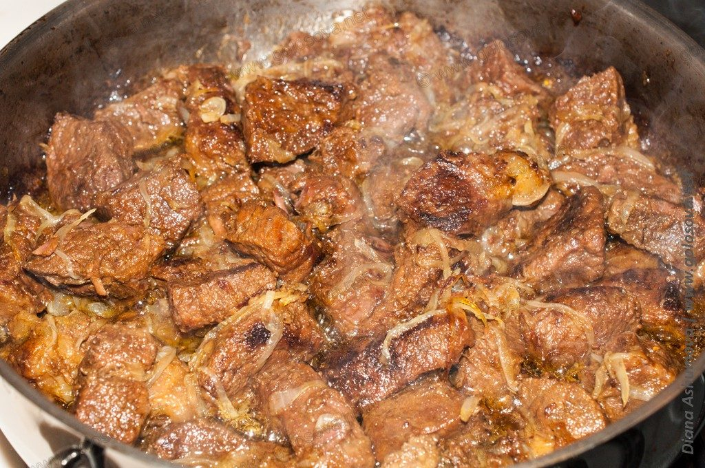 тушеное мясо с луком в сковороде