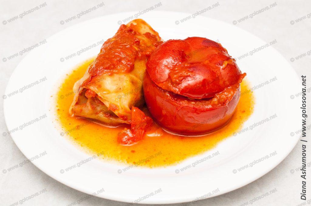 голубец и фаршированный помидор на тарелке с подливой