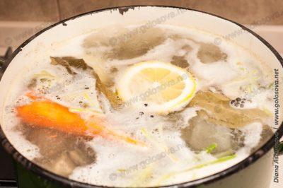 рыба варится с лимоном, морковью и кореньями петрушки